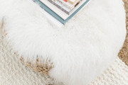 An overhead of books on a side table covered in a sheepskin.