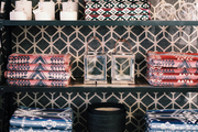 Decorative accessories on shelves backed by a black-and-white pattern
