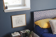 An eclectic Brooklyn bedroom is painted a deep blue and accented with yellow pillows and a printed headboard.