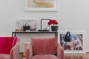 A pink velvet sofa chair with abstract paintings behind it.