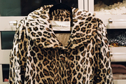 A leopard-print coat hung from a Lucite handle