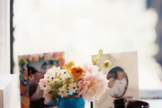 Framed photos and a vase of flowers atop a window sill