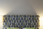 A drum-shade light fixture hung above a patterned headboard