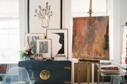 A painting on an easel surrounded by Lucite and art