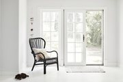 A black rattan chair in a white room.