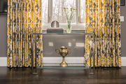 Yellow and gray curtains behind a glass and chrome console table.