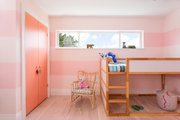 A kid's room with pink striped walls.