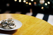 A dish of silver ornaments on a wooden table