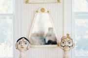 A pair of busts atop a painted cabinet against striped walls