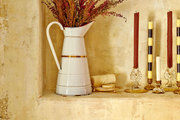 A ledge in a rustic master bath houses a pitcher a mix of candle holders
