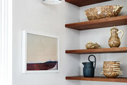 "Martinez' custom kitchen shelves feature assorted ceramics passed down from her grandmother. ""They were handmade in the South of France,"" she explains."