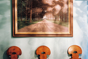 A trio of antique wooden chairs below a landscape painting