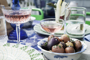 Vintage champagne coupes and a bowl of roasted potatoes on an outdoor table