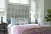 A throw pillow, bolster pillow, and kantha quilt in a master bedroom