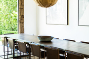 A pendant lamp above a dining table and chairs