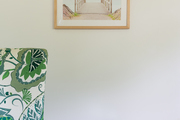 A detail of a framed photograph above a green and white chair.