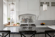 White cabinetry and black marble countertop in traditional kitchen.