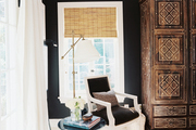 An upholstered chair and a black tulip-style side table with a brass floor lamp