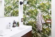 A bathroom with palm wallpaper.