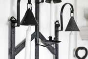 Black metal candle holders hanging on a white wall.