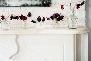 A grouping of bud vases on a white mantel below a mirror