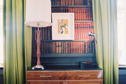 Green curtains flanking shelves of antique books
