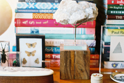 Decorative objects and stacks of books atop a wooden surface