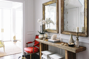 A wooden entryway console with twin mirrors, armchairs and stools; a zebra rug; and herringbone floors