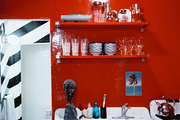 Open shelving and red lacquered walls in a kitchen