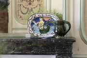 A decorative painted plate on a marble fireplace mantel.