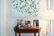 Art hung above a wooden table topped with framed photos