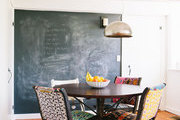 A dining nook with a chalkboard wall and fabric-upholstered seats
