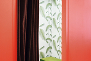 Palm-frond wallpaper and a green bench inside a dressing room