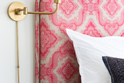 A pink-patterned headboard with a gold sconce.