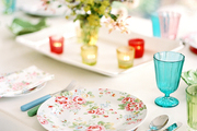 A dining table set with colorful flatware and floral dishes