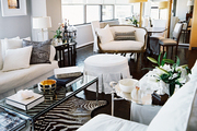 An open living-dining space with white furniture and a zebra-hide rug