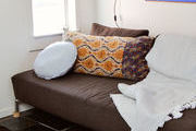 A brown couch with a printed throw pillows and white blanket.