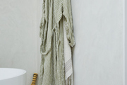 A striped robe and towel hanging in a bathroom.