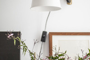 Gathered flowers beneath a wall mounted lamp