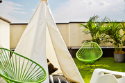 A tepee, two Baby Acapulco Chairs in Cactus, and an Eames elephant on a rooftop patio covered with synthetic lawn