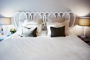 A caned headboard with white bedding flanked by crystal lamps
