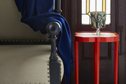 A wood armchair with nailhead  trim draped in a navy throw beside a red wicker-top quatrefoil side table.