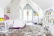 An all-white kid's room  with sun-lit French doors