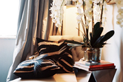 A faceted mirrored table beside a tufted chair covered with zebra-hide pillows