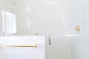 A white and gray shower with gold faucet.