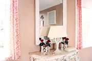 A white carved-wood console between red floral curtains