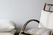 Poised on a shaggy carpet, a vintage twig chair is accented by pillows from Ralph Lauren Home.