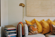 Detail shot of modern sofa with yellow accent pillows, books, floor lamp and wall art.
