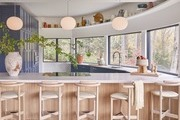 Modern kitchen with timber accents, bar stools, and pendant lighting.