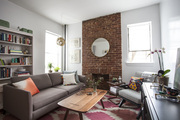 An exposed brick fireplace anchors a white walled Brooklyn living room